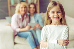 Granny, mom and daughter. Little girl is looking at camera and smiling, in the background her mom and granny are using a tablet while sitting on sofa at home royalty free stock images