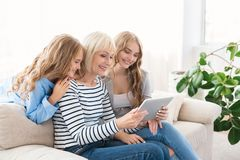 Granny, mother and child using digital tablet at home royalty free stock images