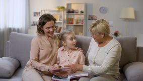 Granny and mother showing photo album pictures to small girl, family history. Stock footage stock video footage