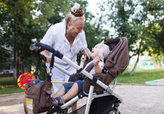 Granny playing with her grandson in pram Stock Photos