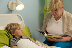 Granny reading grandson book. Granny sitting at bed and reading grandson book royalty free stock photo