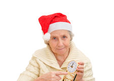 Granny in red Santa Claus hat and clock Stock Photos