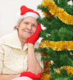 Granny in red Santa Claus hat and red mittens Royalty Free Stock Photo