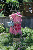 Granny's Flower. An old granny in straw hat and house dress waters her garden Royalty Free Stock Photography