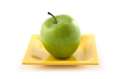 Granny Smith apple. On yellow ceramic plate isolated on white background Stock Photo