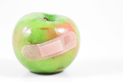 Granny Smith apple and band aid. Stock Photos