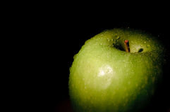 Granny Smith apple on black. Granny Smith apple isolated on black, with water drops Royalty Free Stock Photography