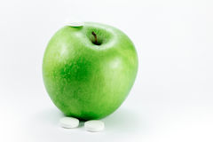 Granny smith apple with pills. A granny smith apple with a three pills on a white background Royalty Free Stock Image