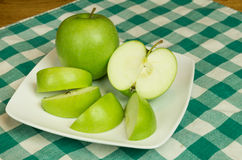 Granny Smith apple slices on white plate Stock Photos