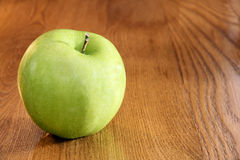 Granny smith apple on table. Healthy food: vibrant green granny smith apple on wooden kitchen table with copy space Royalty Free Stock Image