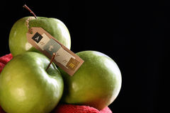 Granny Smith Apples still life. Three green granny smith apples on black background with tag which says autumn Royalty Free Stock Photography