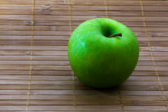 Green granny smith apple on bamboo  Stock Photography