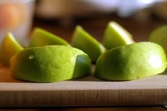 Granny smith pieces on chopping block, cutting board Royalty Free Stock Image