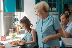 Granny teaches granddaughter to cook royalty free stock images
