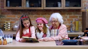 Granny with two granddaughters reading recipe. From cooking book and cooking salad stock video footage