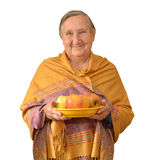 Granny in yellow tippet is holding a plate with apples. Stock Images
