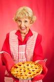 Grannys Home-baked Cherry Pie. Sweet retro grandmother holding a beautiful homemade cherry pie Stock Photo