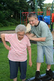 Grannytipping 3. Teenage boy and his grandmother engaged in horseplay at a public playground Stock Images