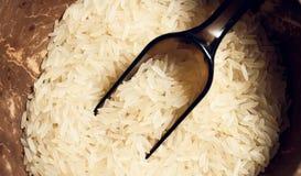 Grano crudo del arroz en placa marrón con la cuchara Imagen de archivo