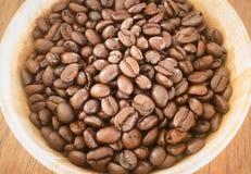 Grano de café asado en cuenco Foto de archivo