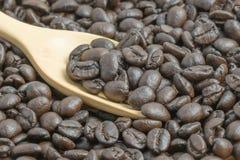 Grano de café con la cuchara de madera Imágenes de archivo libres de regalías