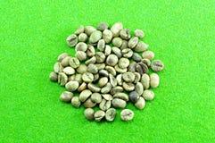 Grano de café crudo en fondo verde Imagen de archivo libre de regalías