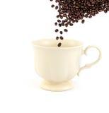 Grano de café de Rosted que cae abajo en té o café vacío del vintage Fotografía de archivo