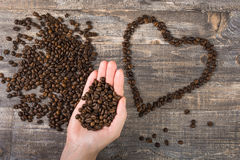 Grano de café a disposición y corazón una tabla de madera Fondo hermoso Imágenes de archivo libres de regalías