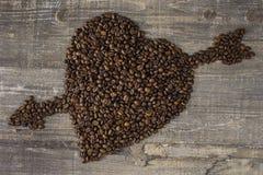 Grano de café a disposición y corazón una tabla de madera Fondo hermoso Fotografía de archivo libre de regalías