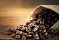 Grano de café en bolso de la harpillera en la tabla de madera Imagen de archivo