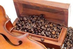Grano de café en una caja del pecho con el violín viejo foto de archivo libre de regalías