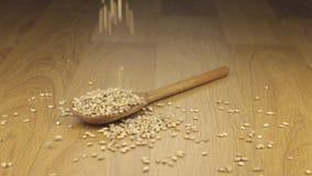 Grano de la cebada de perla que cae en la cuchara de madera que miente en una superficie de madera metrajes