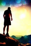 Grano de la película El turista delgado en pantalones en el acantilado del imperio de la roca está mirando abajo al valle de la m Imagen de archivo