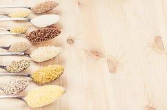 Grano dei cereali diversi in cucchiai con sfuocatura sul bordo di legno beige, fondo sano dell'alimento Immagini Stock