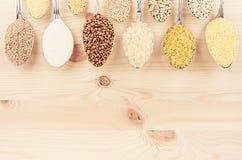 Grano dei cereali diversi in cucchiai sul bordo di legno beige come fondo decorativo Immagine Stock Libera da Diritti