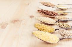 Grano dei cereali diversi in cucchiai sul bordo di legno beige, fondo rustico Fotografie Stock