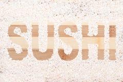 Grano del arroz Sushi de la palabra escrito en tabla de cortar de madera Foto de archivo libre de regalías