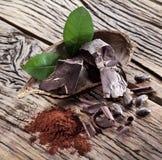 Grano del chocolate y de cacao sobre de madera Fotos de archivo