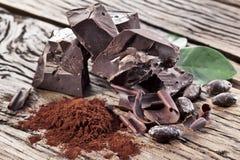 Grano del chocolate y de cacao sobre la tabla Imagenes de archivo