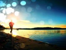 Grano del film Uomo corrente Corridore dello sportivo, tipo pareggiante durante l'alba sopra la spiaggia sabbiosa Fotografia Stock Libera da Diritti