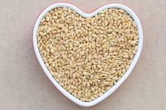 Grano del grano nel piatto di porcellana a forma di del cuore Fotografie Stock