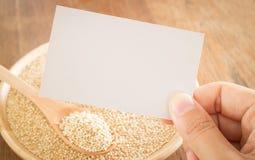 Grano e mano organici della quinoa sul biglietto da visita Fotografie Stock
