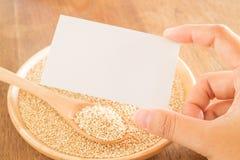 Grano e mano organici della quinoa sul biglietto da visita Fotografia Stock