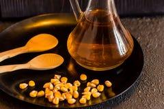 Grano ed olio del cereale in decantatore con i cucchiai di legno Fotografia Stock