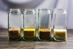 Grano, mijo, guisantes y arroz del alforfón en los tarros de cristal imagenes de archivo