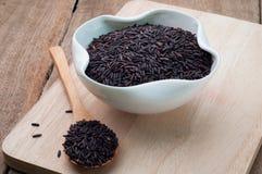 Grano negro del arroz orgánico en la placa blanca en un verraco de madera del corte Imagen de archivo