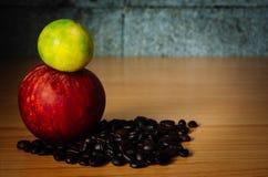 Grano rojo de Apple, de la cal y de café en una madera Imagen de archivo