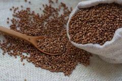 Grano sano del alforfón en un bolso de lino y cuchara de madera en el fondo ligero, foco selectivo Comida orgánica y nutritiva, g Foto de archivo