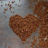 Grano sano del grano saraceno nella forma di cuore su fondo d'annata, vista superiore Il pasto organico e nutriente, glutine libe Immagine Stock