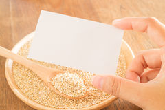 Grano y mano orgánicos de la quinoa en tarjeta de visita Foto de archivo